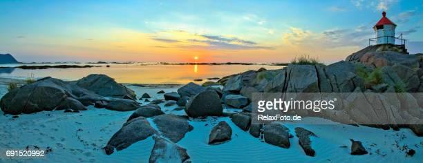 ロフォーテン諸島、ノルウェーのフィヨルドに輝く真夜中の太陽