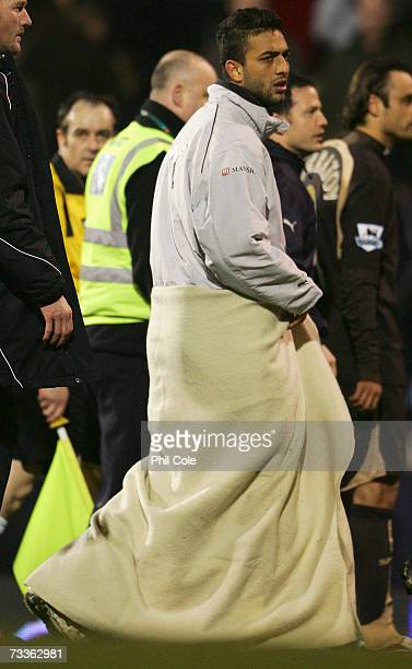 Mido of Tottenham Hotspur wears a blanket to keep warm following the FA Cup sponsored by EON 5th Round match between Fulham and Tottenham Hotspur at...