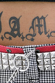 Midriff of woman with studded belt and tattoo on stomach, close-up