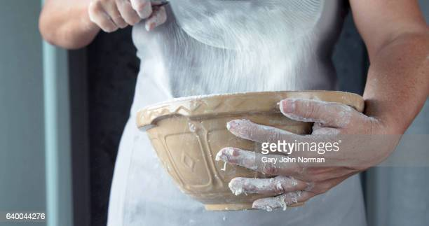Midsection female baker holding mixing bowl close to her body