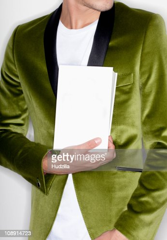 Midsection of a man holding a book