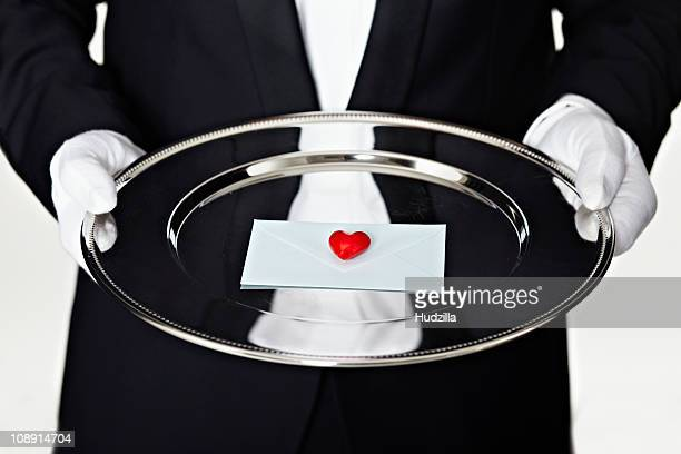 Midsection of a man in a tuxedo holding a letter on a silver platter