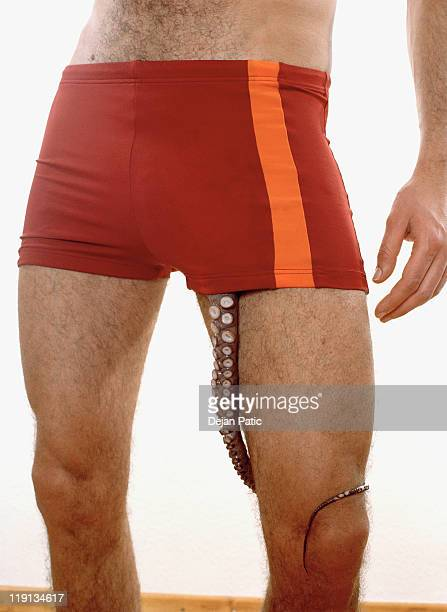 Midsection of a man with an octopus tentacle coming out of his shorts