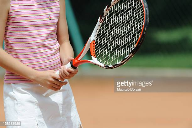 Mid-Section Of A Young Girl Holding Racket