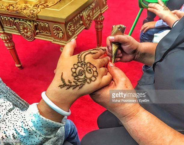 Midsection Of Artist Making Henna Tattoo On Woman Hand