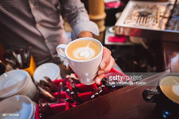 Midsection Of Barista Holding Coffee Cup At Cafe