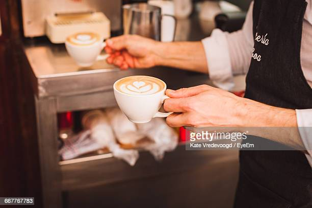 Midsection Of Barista Holding Coffee Cups At Cafe