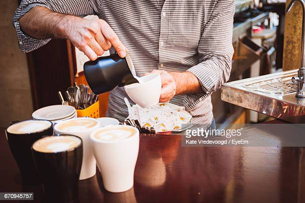 Midsection Of Barista Pouring Cream In Coffee Cup At Cafe