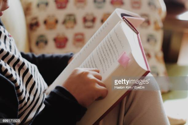 Midsection Of Boy Reading Book While Sitting At Home