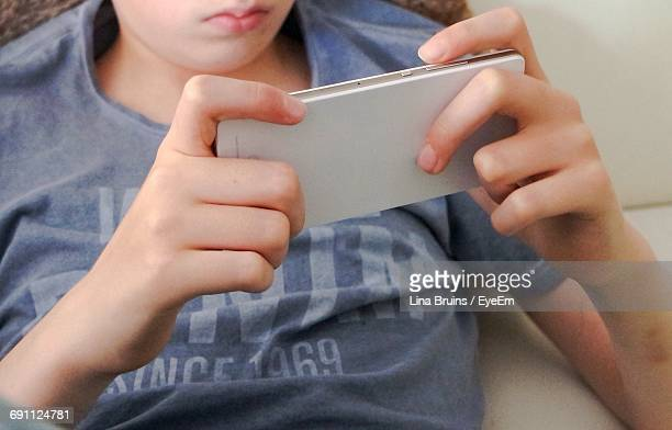 Midsection Of Boy Using Mobile Phone