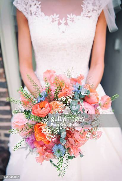 Midsection Of Bride Holding Bouquet Of Flowers