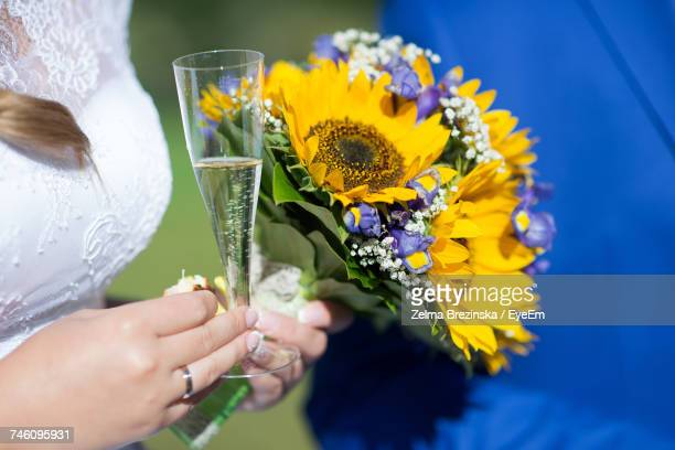 Midsection Of Bride Holding Champagne Flute And Bouquet