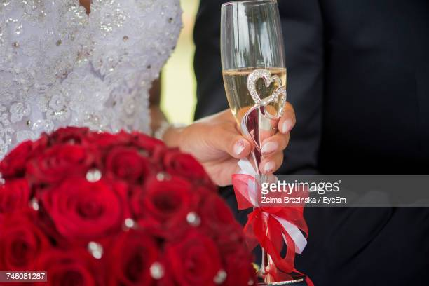 Midsection Of Bride Holding Champagne Flute And Red Roses During Wedding