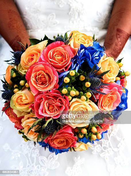 Midsection Of Bride Holding Colorful Rose Bouquet