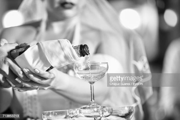 Midsection Of Bride Pouring Wine In Glass