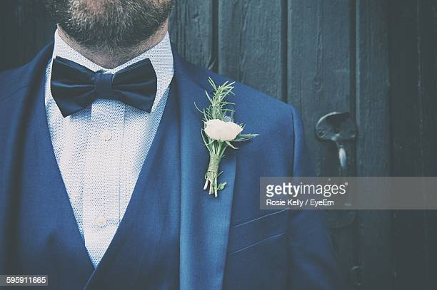Midsection Of Bridegroom Wearing Suit With Boutonniere