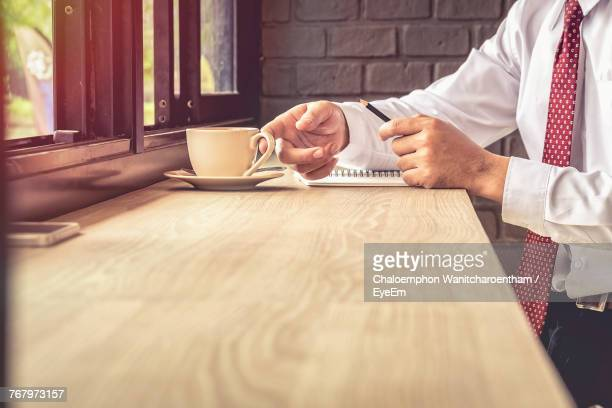 Midsection Of Businessman Having Coffee In Restaurant