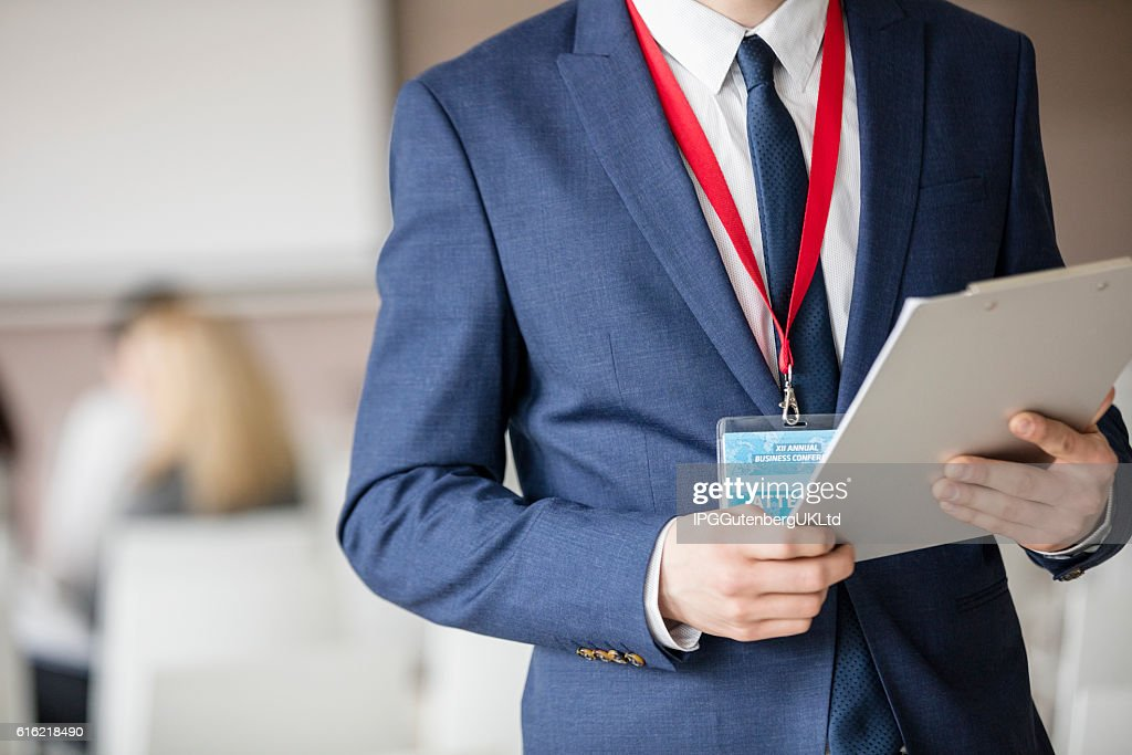 Midsection of businessman holding clipboard in seminar hall : Stockfoto