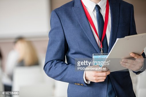 Midsection of businessman holding clipboard in seminar hall : Stock-Foto