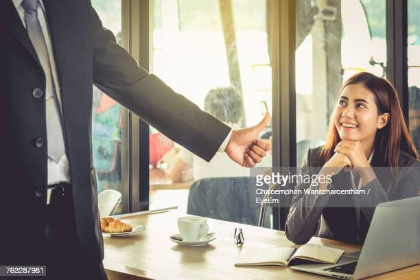 Midsection Of Businessman Showing Thumbs Up To Smiling Female Colleague At Cafe