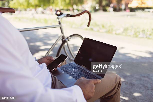 Midsection of businessman using laptop and smart phone while sitting on park bench