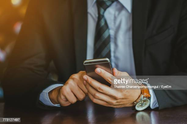 Midsection Of Businessman Using Phone On Table