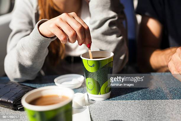 Midsection of businesswoman stirring coffee in train
