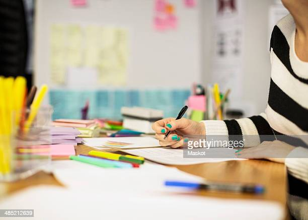 Midsection of businesswoman working at desk in creative office