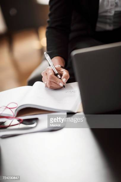 Midsection of businesswoman writing in book on table at hotel room
