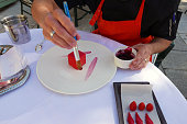 Midsection Of Chef Decorating Dessert Plate On Table