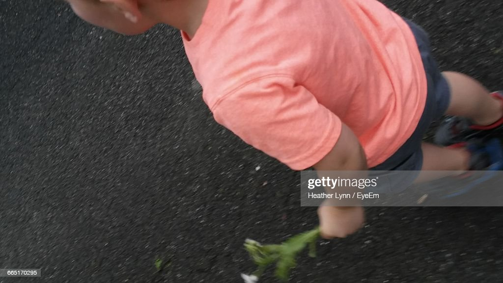 Midsection Of Child Holding Flower