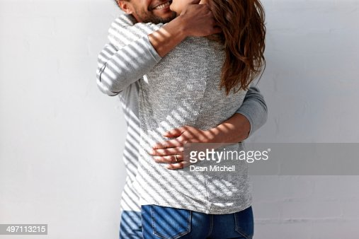 Mid-section of couple embracing against wall : Stock Photo
