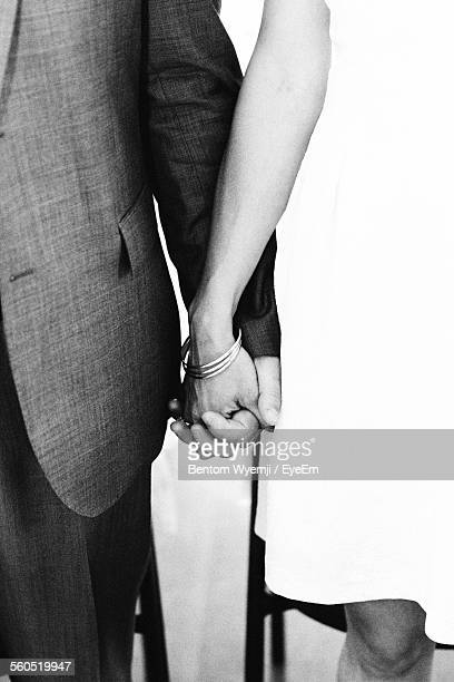 Midsection Of Couple Holding Hand Of Each Other