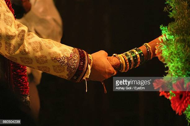 Midsection Of Couple Holding Hands Against Black Background During Wedding