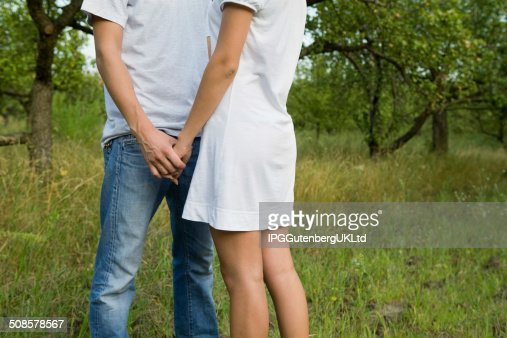 Midsection Of Couple Holding Hands In Orchard : Bildbanksbilder