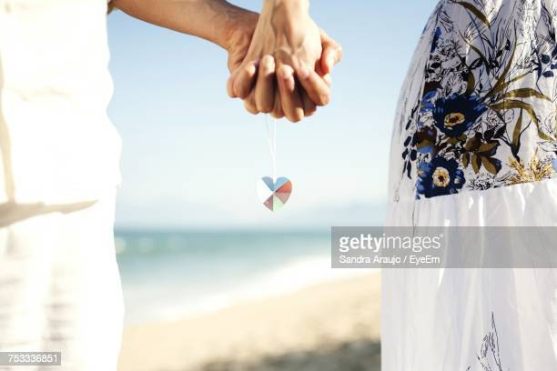 Midsection Of Couple Holding Hands With Love Locket Chain At Beach