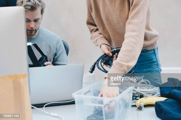 Midsection of female computer programmer removing cables from container while colleague holding headphones in office
