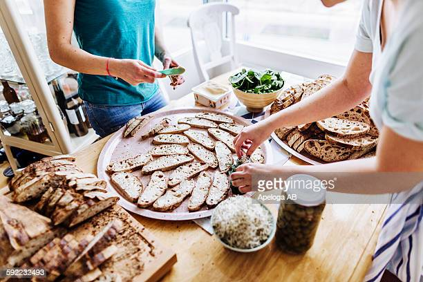 Midsection of female friends preparing open faced sandwiches at table