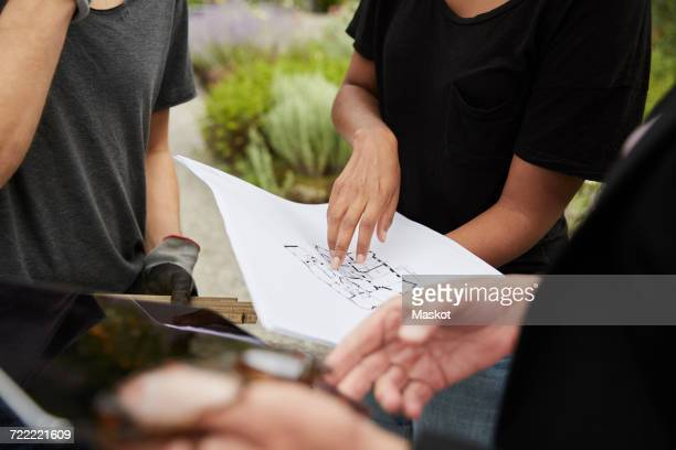 Midsection of female garden architect explaining blueprint to colleagues