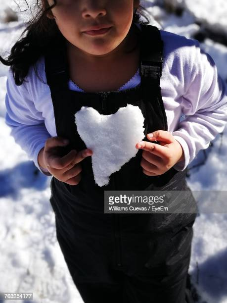 Midsection Of Girl Holding Heart Shape Snow While Standing On Field
