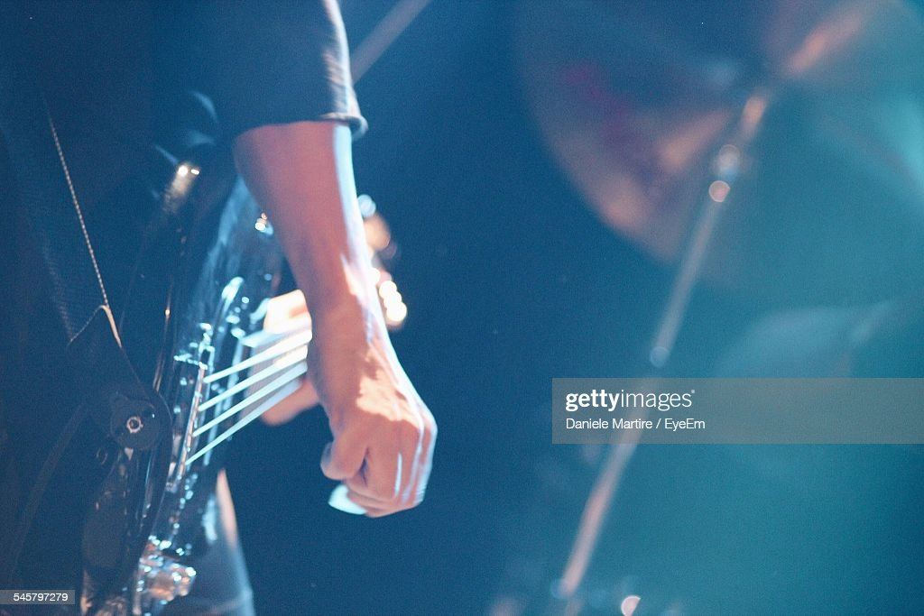 Midsection Of Guitarist Playing Bass Guitar On Stage