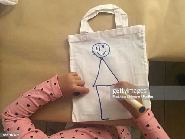 Midsection Of Kid Drawing On White Bag At Home