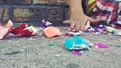 Midsection Of Kid Touching Confetti On Footpath