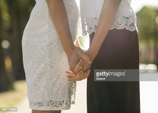 Midsection of lesbian couple holding hands