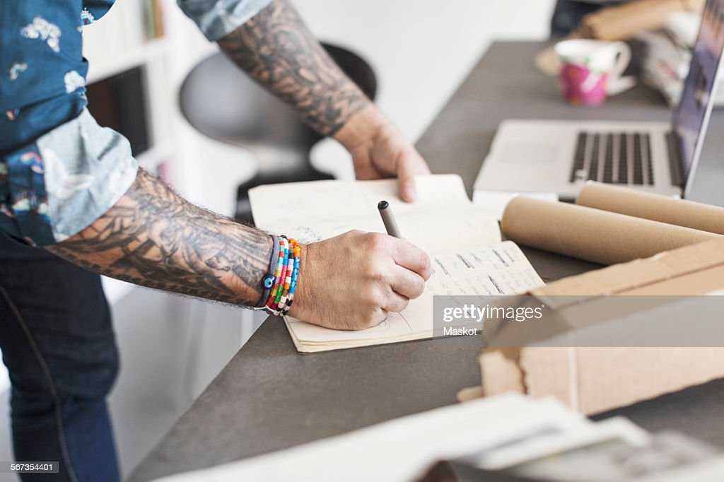 Midsection of male architect writing in book at table