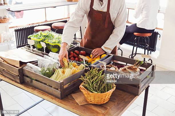 Midsection of male owner arranging vegetables at grocery store