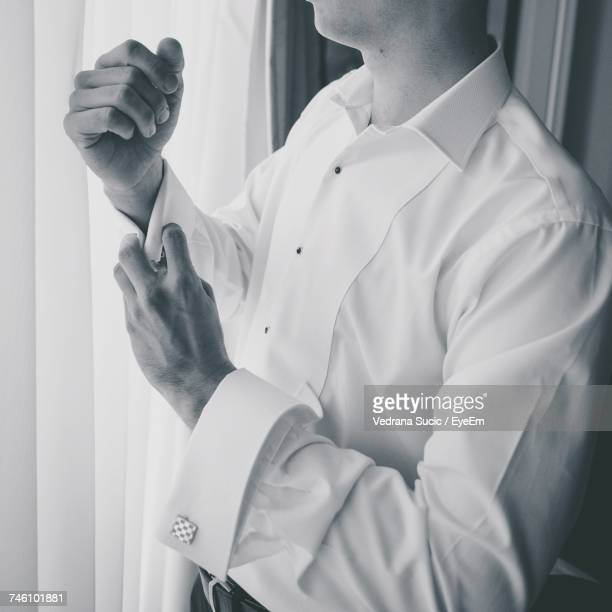 Midsection Of Man Adjusting Cuff Links By Curtain
