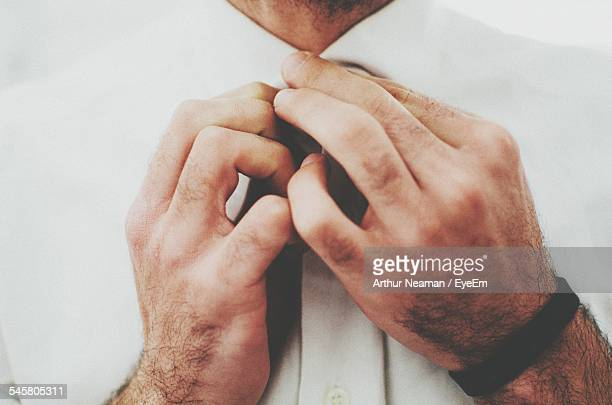 Midsection Of Man Buttoning Shirt