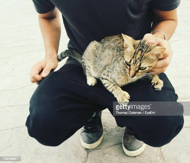Midsection Of Man Carrying Cat While Crouching Outdoors