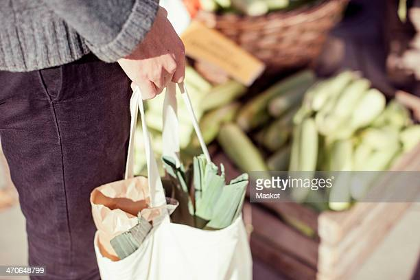 Midsection of man carrying vegetable bag in market